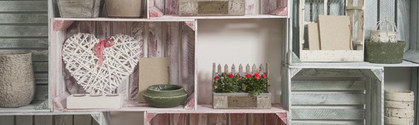Holzkisten gestapelt und arrangiert als Wand mit Dekoelementen und Blumen verziert