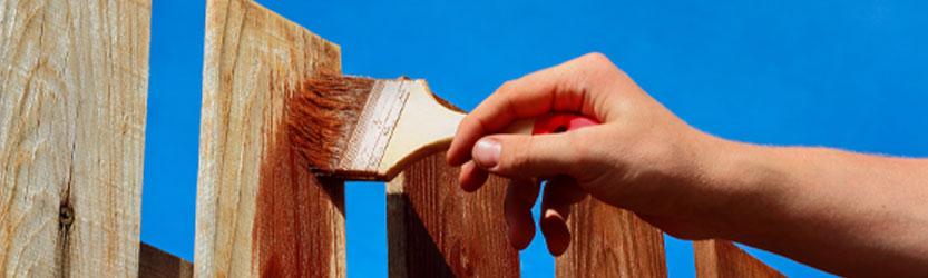 Hand die Zaun mit Pinsel streicht