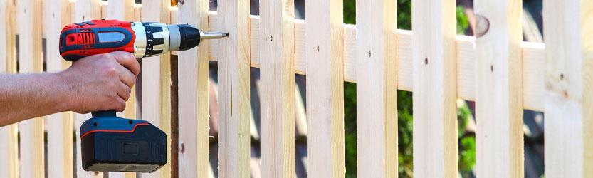 Akkuschrauber in der Hand einer Person, die einen Gartenzaun aus Holz zusammenbaut